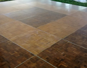 Close up view of portable parquet wood flooring assembled into a 18′ x 18′ dance floor under a tent.