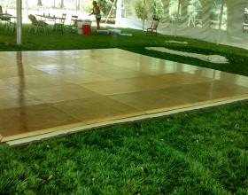 Portable parquet wood flooring assembled into a 18′ x 18′ dance floor under an event tent.