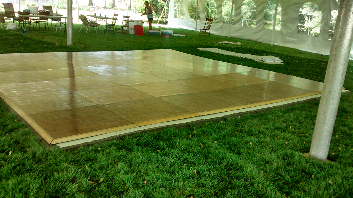 Portable Parquet Wood Flooring Assembled Into A 18u2032 X 18u2032 Dance Floor Under  An Event Tent.