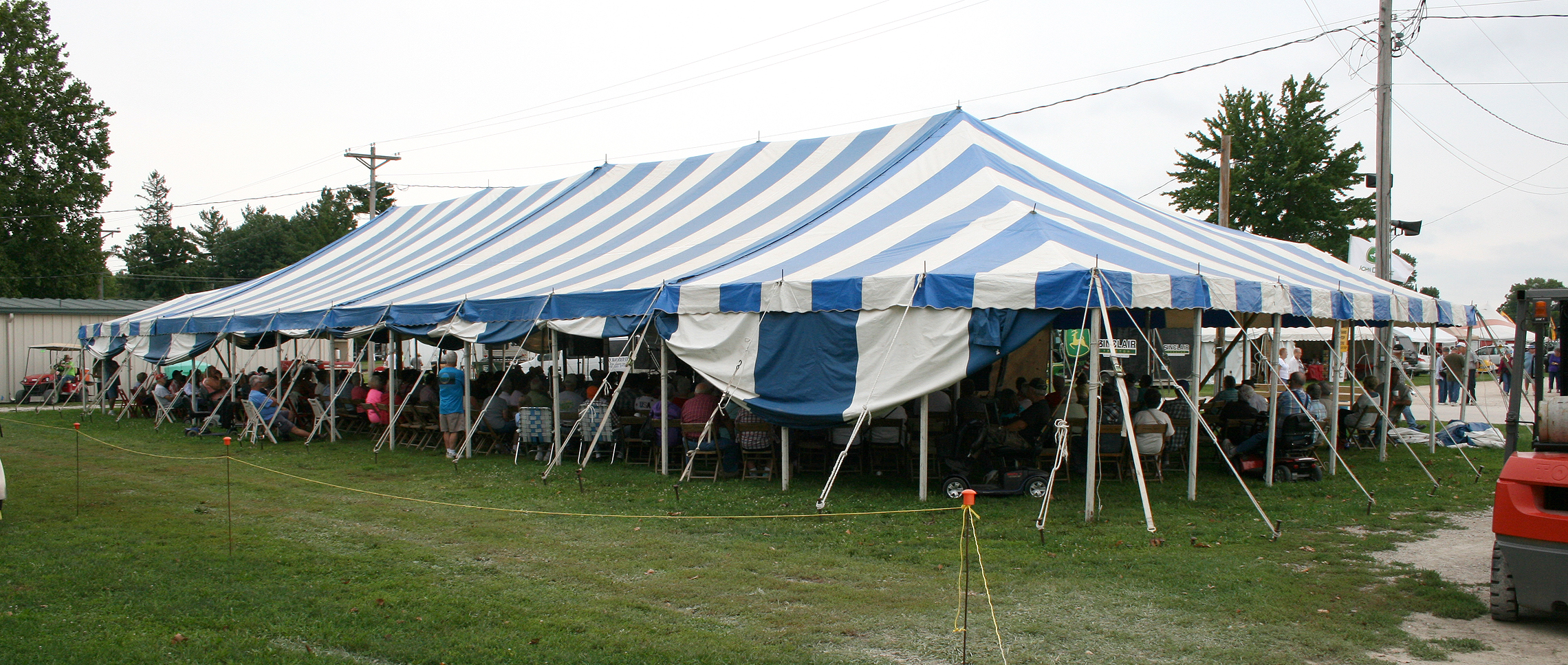 40u2032 x 100u2032 blue and white rope and pole tent with stage & 2014 Midwest Old Threshers setup by Big Ten Rentals