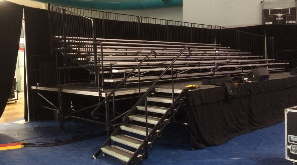 7 Row by 32 feet long granite expandable breakdown bleacher system setup on stage. Elevated for pictures and better viewing.