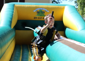 Boy adding marker on bungee run challenge inflatable