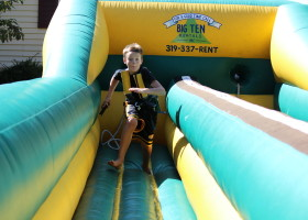 Boy running on bungee run challenge inflatable