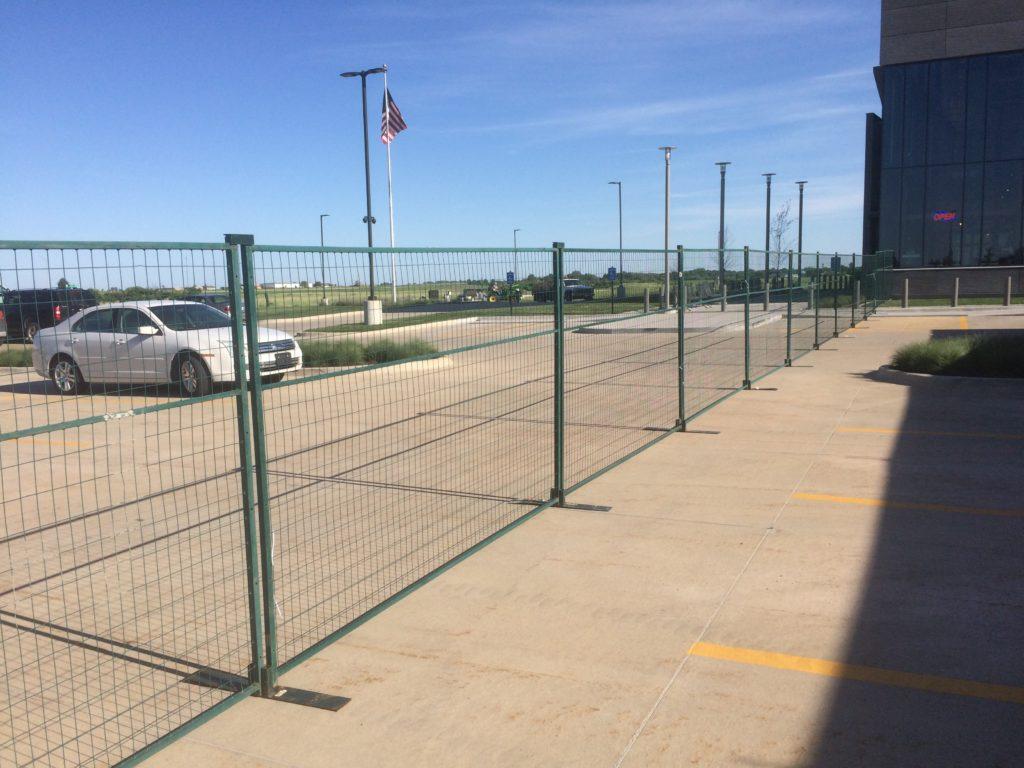Green temporary security fencing. Event perimeter barricade