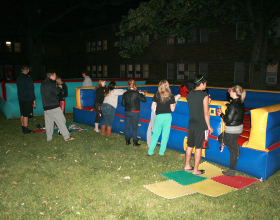 Group of people around inflatable twister game