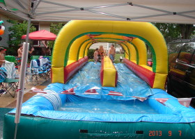 Kids playing on dual lane slip 'n slide inflatable