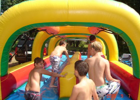 Kids walking on dual lane slip 'n slide inflatable