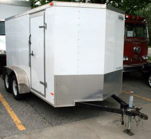 Left front view of our 6' x 12' enclosed cargo box utility trailer.