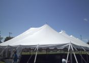 Staking at the corner of the 80′ x 150′ Rope and Pole event tent.