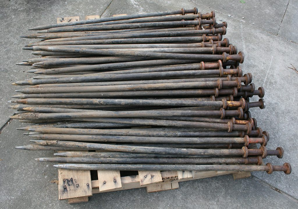 Massive 1' tent stakes used as tent anchors/ballast that are so long they are hanging off of a wooden pallet.