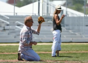 Kevin Costner plays catch with his son at the 25th anniversary of the movie Field of Dreams in Dyersville, Iowa with Bleachers by Big Ten Rentals in the background.