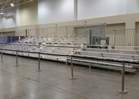 45′ towable hydraulic bleacher flanked by two 5-row bleachers, stanchions, plus pipe and drape.
