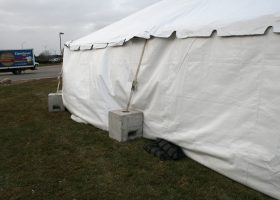 "Frame tent with ""Block and Roll"" ballast and sand bags to hold down the sidewalls in the wind."