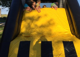 Children at the top of the slide on the mini loader inflatable combo bounce house