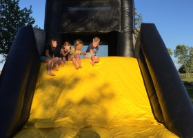 Four children at the top of the slide on the mini loader inflatable combo bounce house