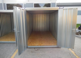 Open door to large portable temporary steel storage shed