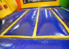 Floor of the mini rainbow bounce house and slide combo