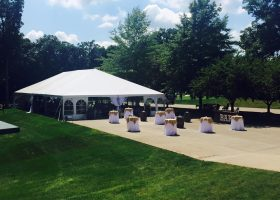 Outside of wedding tent with tables wine barrels and bar