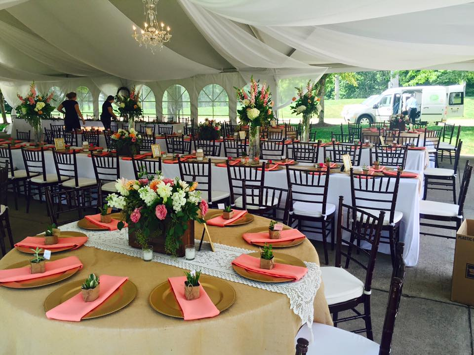 Tables and chairs setup under wedding tent with drape and chandeliers