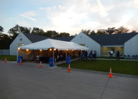 20′ x 50′ frame tent with tables, lights, linens and chairs at Pet Adoption Center