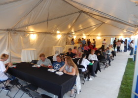 Pictures from under 20′ x 50′ frame tent with tables, lights, linens and chairs at event