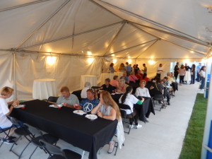 Pictures from under 20' x 50' frame tent with tables, lights, linens and chairs at event