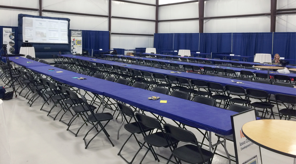 Tables and chairs setup for indoor event with booths in the background