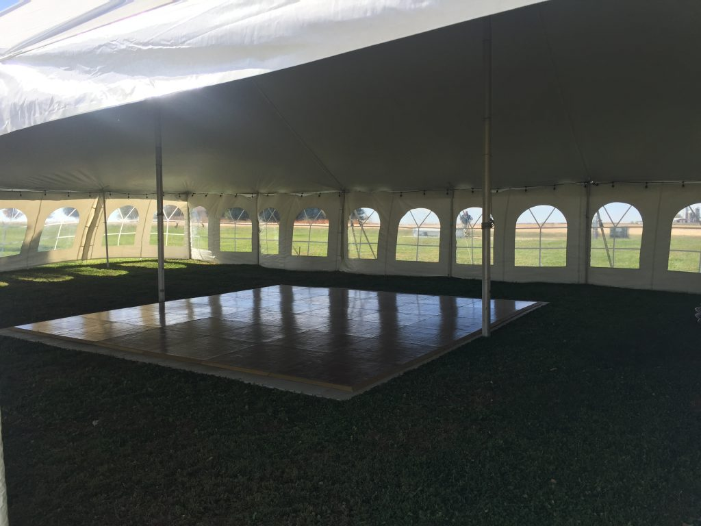 Dance floor with lights under 40x60 rope and pole wedding tent with sidewall in De Witt, Iowa