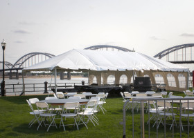 Frame tent with tables and chairs at 2015 River Roots Quad Cities Music and Rib Fest