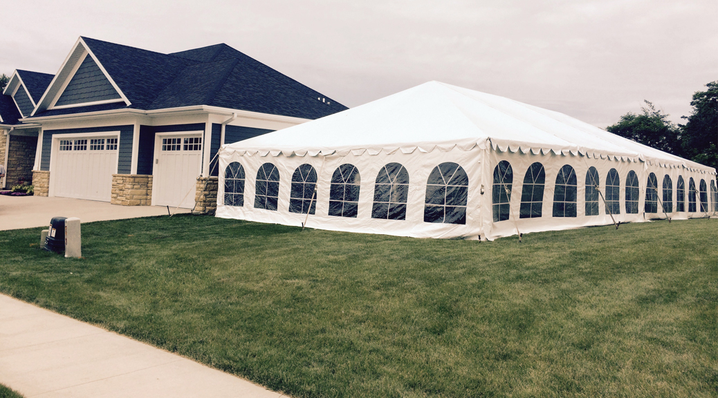 Home with 30' x 60' frame tent in side yard for wedding reception in Dubuque, Iowa