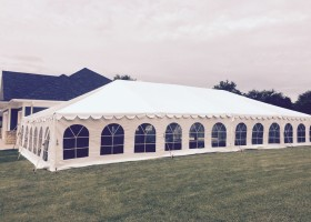 Side of 30′ x 60′ frame tent in side yard for wedding reception next to a home