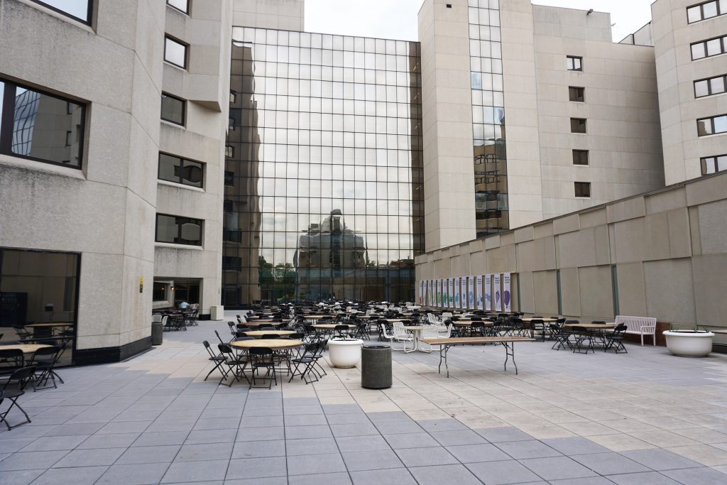 Tables and chairs at University of Iowa Hospitals and Clinics courtyard image from ground