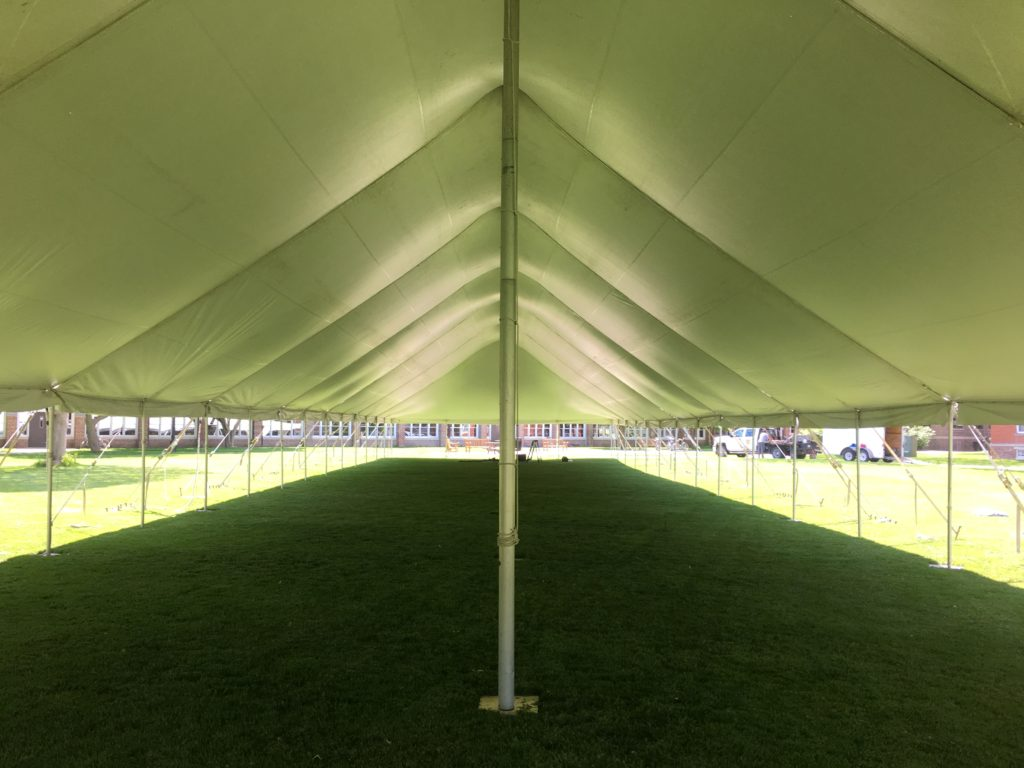Under the middle of a 40' x 160' rope and pole tent for Commencement at Grinnell College 2016