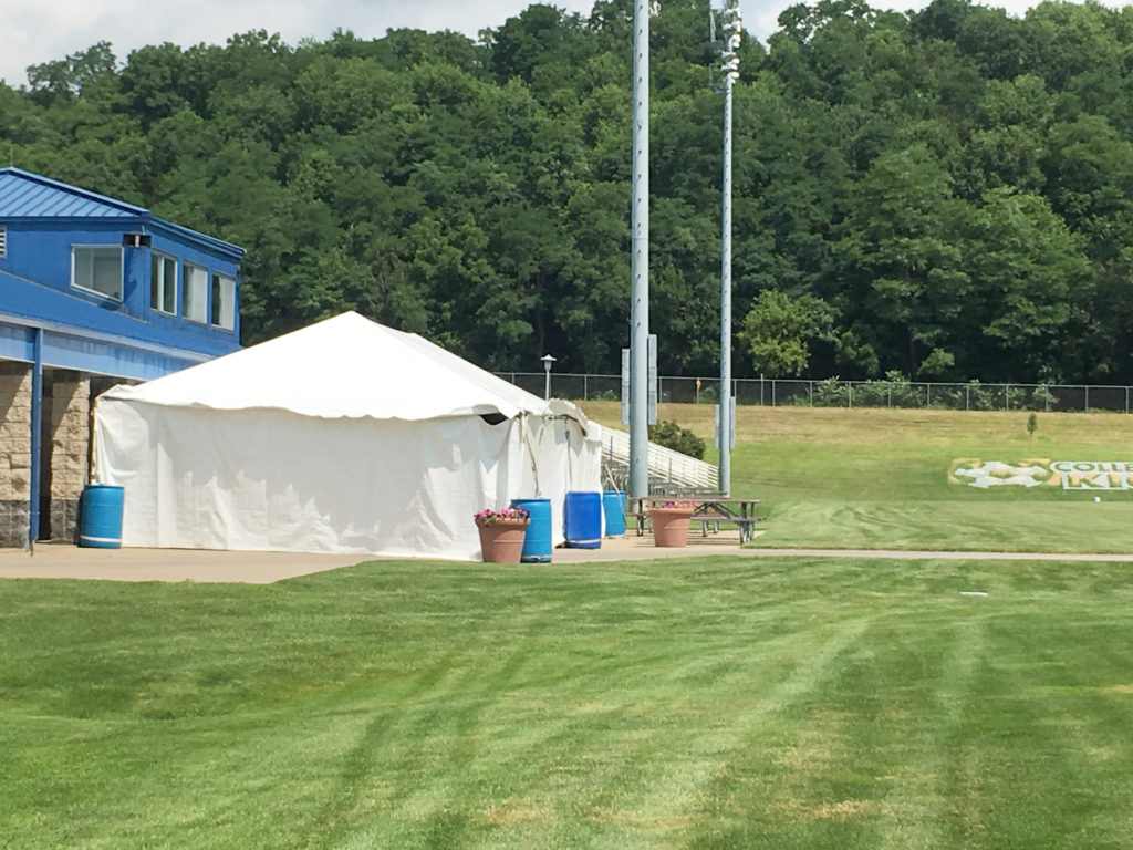 Frame tent with side walls with ballast of water barrels at the Muscatine Soccer Complex