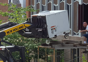 Lifting the rented 12-ton Air Conditioning unit onto the scaffolding with the owner Brian DeCoster on the scaffolding