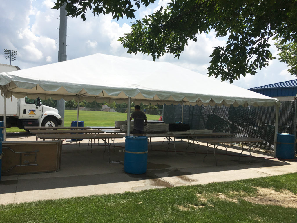 Side of frame tent with water barrels as ballast at Muscatine Soccer Complex
