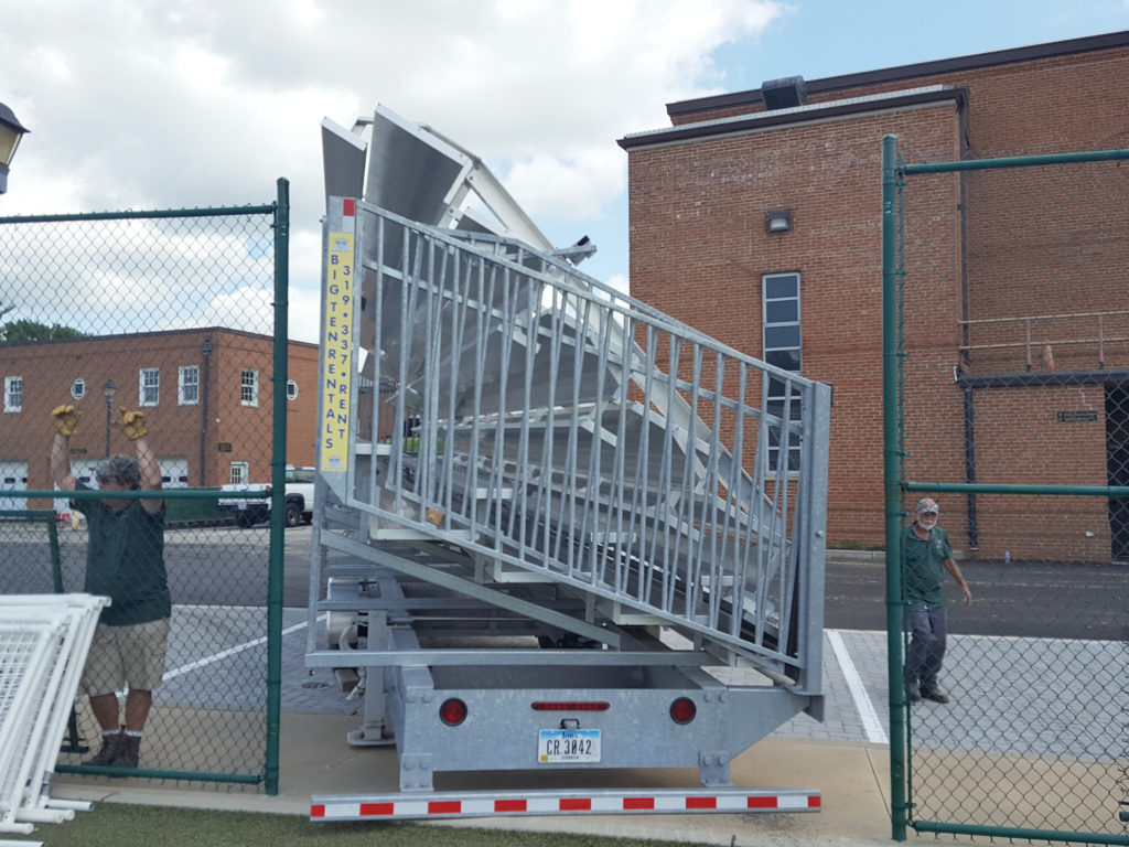 Towable bleachers being delivered though a small gate with spotters