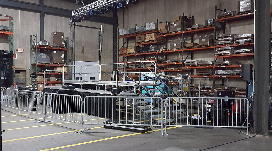 Political event setup with tiered stage, barricade and pipe and drape parts at Giese Manufacturing