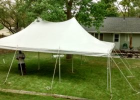 Setting up a 20′ x 30′ rope and pole tent under a tree for a backyard party in Iowa City
