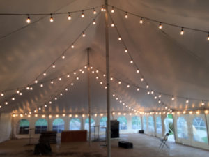 Under 40' x 60' white rope and pole wedding tent at Harvest Preserve with lights