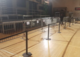 Belt style seat belt stanchions, barricade and stage at political rally