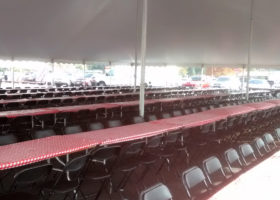 Under our 60′ x 90′ rope and pole tent with tables for seating setup for Morris & Company Entertainment in Davenport, Iowa