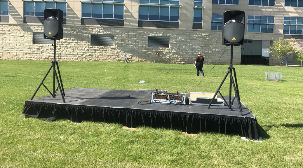 8' x 16' stage with PA Pro Package and tripod stands behind UICCU Financial Center Building in North Liberty, IA