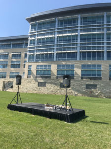 8' x 16' stage with PA Pro Package and tripod stands behind UICCU Financial Center Building in North Liberty, Iowa