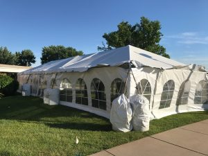 20' x 60' frame tent with French Sidewalls and Water Barrels for a wedding reception at a St John Vianney Church in Bettendorf Iowa