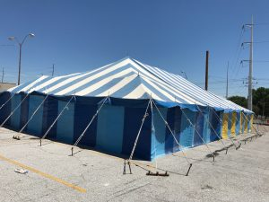 Blue and White 40' x 70' Galla rope and pole tent setup for a fireworks stand in Davenport, Iowa