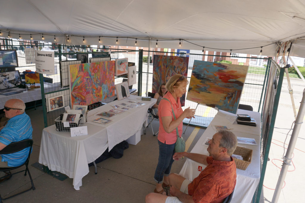Booth of Hannah Zuber at Emerging Artists exhibit tent at Summer of the Arts Festival