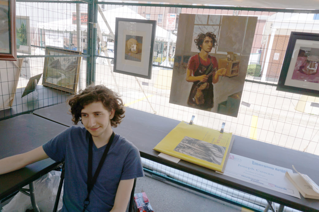 Emerging Artist Joseph Cowan with his self-portrait at the Summer of the Arts Festival