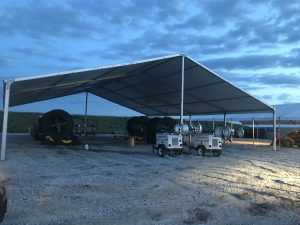 Last minute construction site setup 18m x 20m (60′ x 66)' Clearspan Tent at dusk