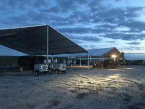 Last minute construction site setup with a 18m x 20m (60′ x 66)' Clearspan Tent on the left and a 40′ x 60′ Clearspan Tent on the right at dusk